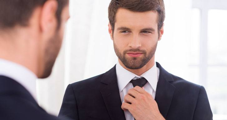 Confident man looking in mirror